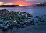 Vancouver Island, British Columbia: Setting sun overa rocky point of MacKenzie Beach near Tofino