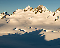Afternoon light over mountain ranges of Southern Alps with Explorer Glacier crevasses in upper parts of Fox Glacier NEVE, Westland Tai Poutini National Park, West Coast, UNESCO World Heritage Area, New Zealand, NZ