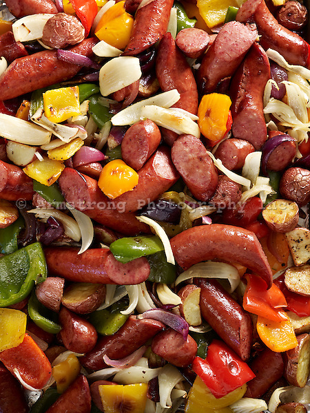A closeup image of mixed grilled foods including kielbasa (Polish sausage), onions, potatoes, red, yellow, and green peppers