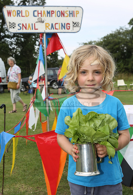 2014 World Championship Snail Racing in Congham (Norfolk)<br /> Picture Description:<br /> Zeben Butler-Alldred, aged 5, from London receive the coveter prize.<br /> The 2014 championships were held on 19th July 2014 and the winner was a snail called Wells owned and trained by Zeben Butler-Alldred, aged 5, from London.&nbsp; Wells completed the course in 3 minutes 19 seconds, a slow time because of the heat. Zeben was on holiday in West Norfolk and named his snail after the local town Wells which he liked.<br /> General info:For more than 25 years the World Snail Racing Championships have been held at Congham, near King's Lynn, in Norfolk.Before snails can enter a race a sticker with a number must be put on so they can be identified. The snails race from the centre of a circle to the outside. The circle has a radius of 13 inches. The snails are put in the middle and pointed in the right direction.The  Snail Master Neil starts the races. He shouts: &quot;Ready, steady, SLOW!&quot; And off dash the snails! The Snail Master keeps the course well-watered as snails like damp conditions.Races are held on a table covered with a white cloth. Machine a circle, with braid in the middle, and then machine a similar circle 13 inches away.Owners do dress up. The World record stands at 2 minutes over the 13 inches. It was set up in 1995 by a snail called Archie. The record can only be challenged at the World Championships at Congham.Giant foreign snails are not allowedOften owners like to give their snails names like Speedy or Schumacher!<br /> Picture by Marcello Pozzetti &copy; IPS PHOTO AGENCY<br /> Cavell Barn<br /> The Common<br /> Swardeston<br /> Norwich<br /> Norfolk<br /> NR14 8DZ<br /> T 01508 571 480<br /> M 07973308835