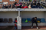 Gornal Athletic 4 Wisbech Town 2, 02/02/2013. Garden Walk Stadium, FA Vase 4th round. The home team's reserve goalkeeper sitting in the dugout while supporters in the seats waiting for the match to start at Garden Walk Stadium, prior to the FA Vase 4th round tie between Gornal Athletic from Dudley in the West Midlands and visitors Wisbech Town. Gornal, from the Midland Alliance and appearing for the first time at this stage of the tournament, defeated Wisbech, who play in the Eastern Counties League, by 4-2 after extra-time, after the visitors had lead two-nil after 10 minutes. The FA Vase was a nationwide, non-League English football tournament for semi-professional clubs and the winner of this tie played away at Bodmin Town in the next round. Photo by Colin McPherson.