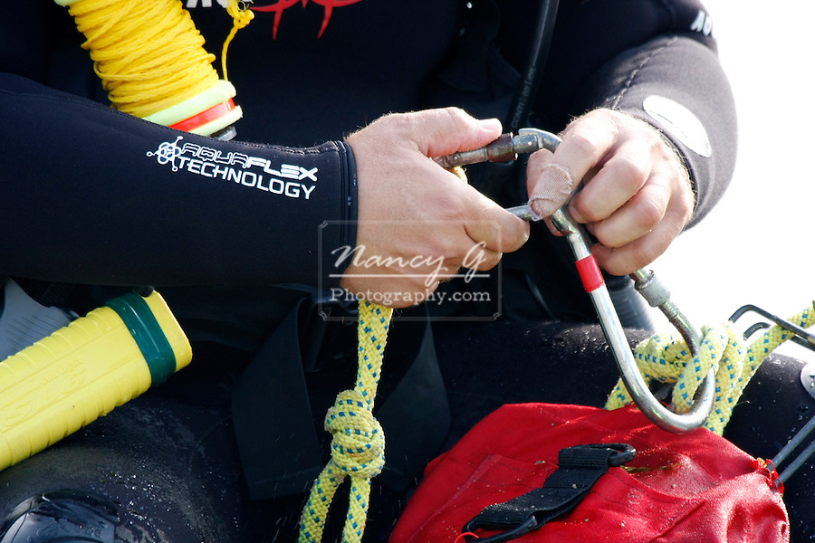 Scuba diver hooking up equipment to dive on a lake