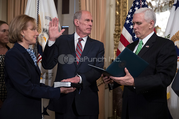 United States Vice President Mike Pence (R) administers the oath of office to Director of National Intelligence Dan Coats (C), with his wife Marsha Coats (L), during a swearing in ceremony in the US Capitol in Washington, DC, USA, 16 March 2017.<br /> Credit: Shawn Thew / Pool via CNP /MediaPunch