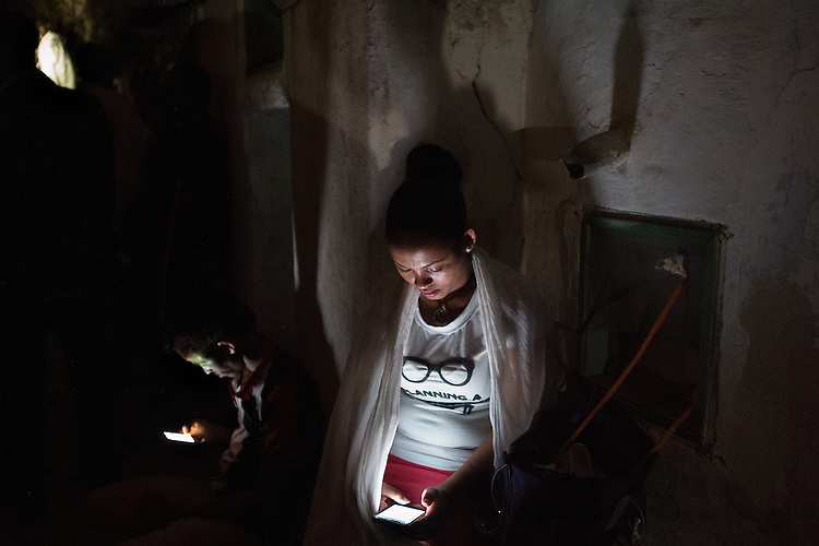 A woman and a man read through their smartphones, as Orthodox-Ethiopian Christian pilgrims gather at Deir Al-Sultan, the Ethiopian section of the Church of Holy Sepulchre in Jerusalem's old city, during the Holy Fire ceremony as part of Easter. The ancient fire ritual celebrates the Messiah's resurrection after being crucified on the cross.