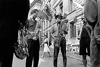 """Switzerland. Geneva. Old town. A band is playing music in the streets on Music Day. Three men play saxophone while another the clarinet. The saxophone (the sax) is a woodwind instrument usually made of brass and played with a single-reed mouthpiece similar to that of the clarinet. The player covers holes by pressing mechanical keys, triggering a system of pads, pivots, and linkages. The clarinet is a family of woodwind instruments. It has a single-reed mouthpiece, a straight, cylindrical tube with an almost cylindrical bore, and a flared bell. A person who plays a clarinet is called a clarinetist. The flag of Geneva with an eagle and a key. The eagle symbolises loftiness, justice and protection. The key symbolises ecclesiastical rule, treasuries, and responsibility. The arms of Geneva are actually two shields impaled: half the eagle of the Holy Roman Empire, and one of the two keys of St. Peter (the """"keys of heaven""""). The Fête de la Musique, also known in English as Music Day, Make Music Day or World Music Day, is an annual music celebration that takes place on 21 June ( but usually during the previous or following weekend). On Music Day the citizens of a city or country are allowed and urged to play music outside in their neighborhoods or in public spaces and parks. Free concerts are also organized, where musicians play for fun and not for payment. 22.06.1993 © 1993 Didier Ruef"""