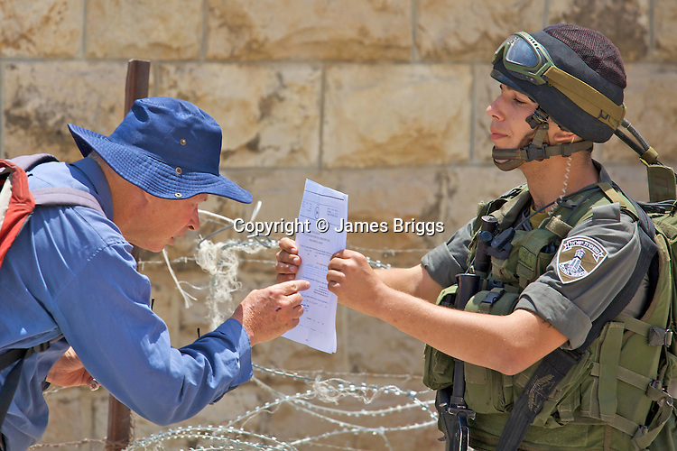 An Israeli activist reaches over a barbed wire barrier at a road block in order to study a document held by an Israeli border police officer designating the area a closed military zone during a non-violent demonstration against Israel's controversial separation barrier in the West Bank town of Beit Jala, near Bethlehem on 11/07/2010.