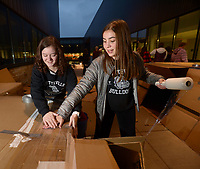 NWA Democrat-Gazette/ANDY SHUPE<br /> Elizabeth Gunderman (left) and friend Riley Garrison, both 15-year-old freshmen at Fayetteville High School, work together Thursday, Dec. 6, 2018, to seal up their cardboard house during the 20th annual Homeless Vigil at the school. Members of the school's Student Council are spending the night outside to raise awareness and money for the district's Families in Transition Program which serves students and their families in need of assistance.