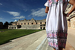A young woman wearing a traditional Yucatan dress Terno in Nuns Quadrangle inside of Maya ruin city Uxmal. Mexico