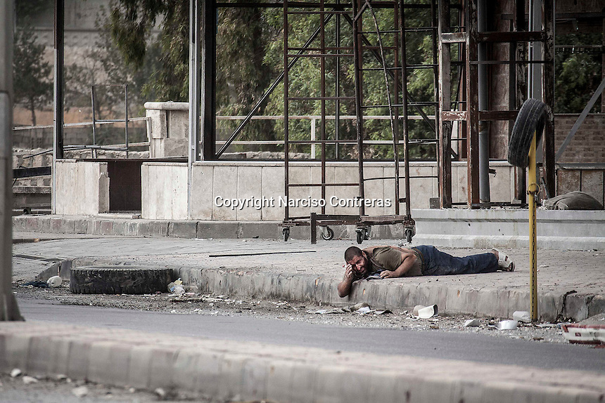 A Syrian civilian lies down on the street as he drags his own body to scape from the line of fire after he was targeted at his back by one Syrian army sniper while was walking at the front line in Bustan Al-Bashar, northeast of Aleppo City.
