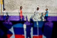 Haitian people on the street seen through the colourful tap-tap bus window in Pétionville, Port-au-Prince, Haiti, 9 July 2008. Tap-tap vehicles serve as public transportation in Haiti. They are private, operate over fixed routes, departing only when full. Tap-taps are decorated with bright and shiny colors and with a lot of fancy designed elements. There are scenes from the Bible, Christian slogans, TV stars or famous football players often painted on a tap-tap body. Tap-tap name comes from sound of taps on the metal bus body signifying a passenger's request to be dropped off.