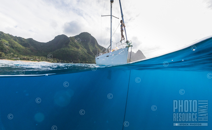 A woman stands on the bow of an anchored sailboat on the Na Pali Coast of Kaua'i.