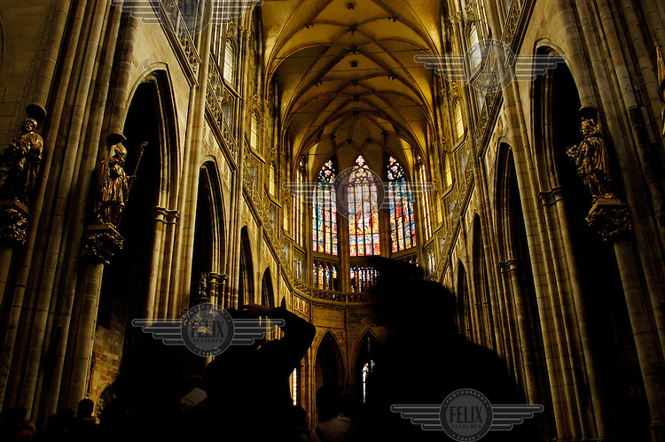 Visitors in the gothic interior of St Vitus Cathedral.