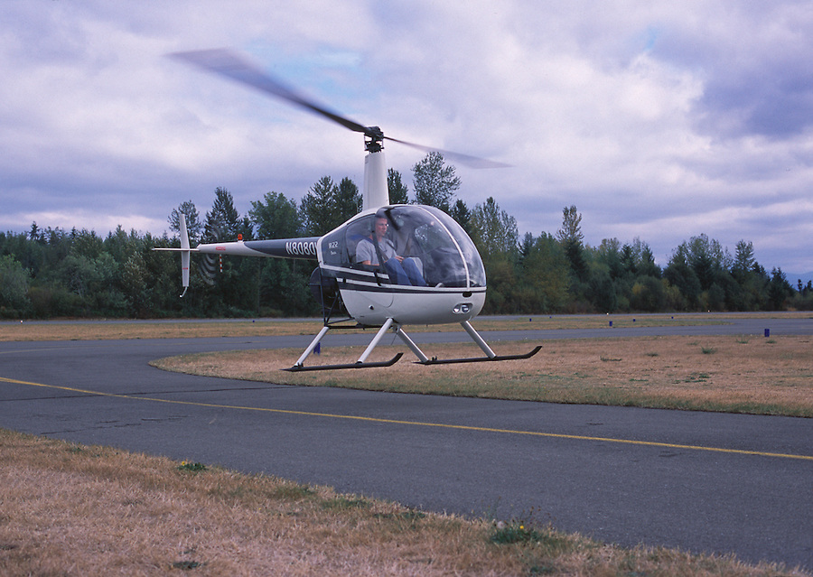A Robinson R22 helicopter taxies up the runway.