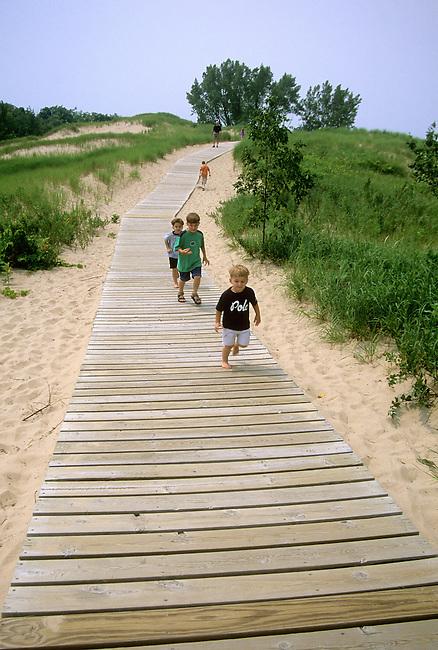 Children run along the boardwalk trail leading to the top of Great Sleeping Bear Dune, 400 plus feet above Lake Michigan, at the Pierce Stocking Scenic Drive Area of Sleeping Bear Dunes National Lakeshore in Leelanau County, Michigan