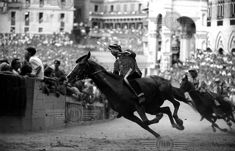 © Francesco Cito / Panos Pictures..Siena, Tuscany, Italy. The Palio. ..Twice each summer, the Piazza del Campo in the medieval Tuscan town of Siena is transformed into a dirt racetrack for Il Palio, the most passionately contested horse race in the world. The race, which lasts just 90 seconds, has become intrinsic to the town's heritage since it was first run in 1597.
