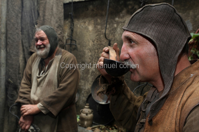 Scene from a street market in the Middle Ages with a man drinking soup from a ladle at a food stall. Image taken from the filming of 'Paris la ville a remonter le temps' written by Carlo de Boutiny and Alain Zenou, directed by Xavier Lefebvre, a Gedeon Programmes production. Picture by Manuel Cohen