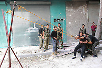 Photographer: Rick Findler..06.10.12 Members of the Free Syrian Army use a make-shift catapult to fire homemade explosives into an area believed to be housing Assad's soldiers in the city of Aleppo.