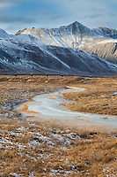 Frozen stream in the tundra of Atigun canyon with the Endicott mountains of the Brooks Range in the distance.