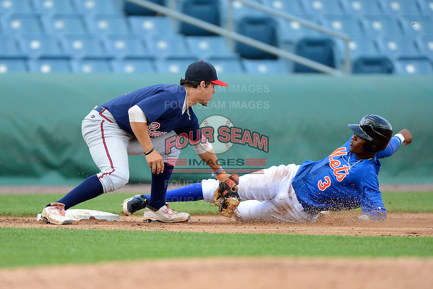 Michael Chavis (1) of Sprayberry High School in Marietta, Georgia playing for the Atlanta Braves scout team during the East Coast Pro Showcase attempts tagging Ti'quan Forbes (3) sliding in safely on July 31, 2013 at NBT Bank Stadium in Syracuse, New York.  (Mike Janes/Four Seam Images)