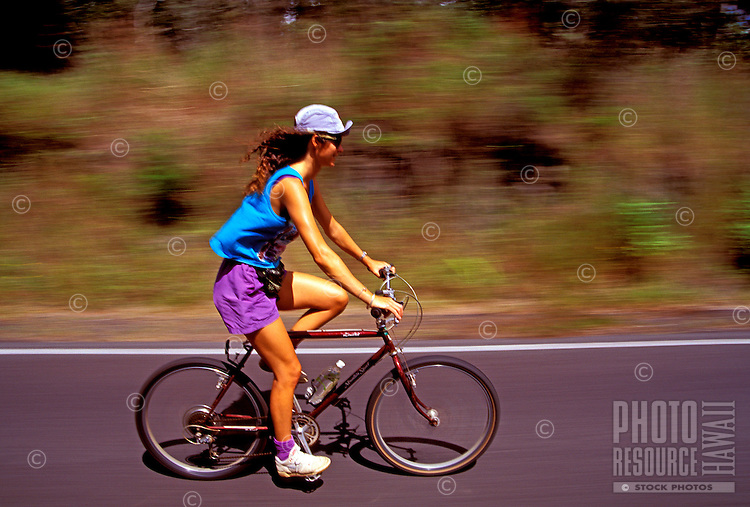 A woman bicycles on a road in Hawaii Volcanoes National Park on the Big Island of Hawaii.