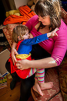 "A woman  7 months pregnant breastfeeds her little girl aged nearly 3 years old on the sofa in her living room. They are playing the  Incy Wincy Spider song/game at the same time.<br /> <br /> Image from the ""We Do It In Public"" documentary photography project collection: <br />  www.breastfeedinginpublic.co.uk<br /> <br /> Dorset, England, UK<br /> 14/02/2013"