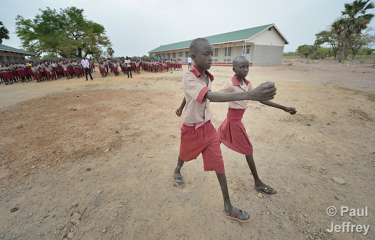 Two students march to raise the flag during a morning assembly at the Loreto Primary School in Rumbek, South Sudan. The Loreto Sisters began a secondary school for girls in 2008, with students from throughout the country, but soon after added a primary in response to local community demands.