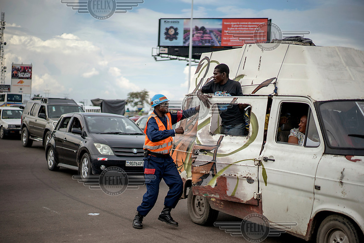 A traffic policeman has an altercation with a passenger in a van who is half hanging out of the side door of the vehicle.