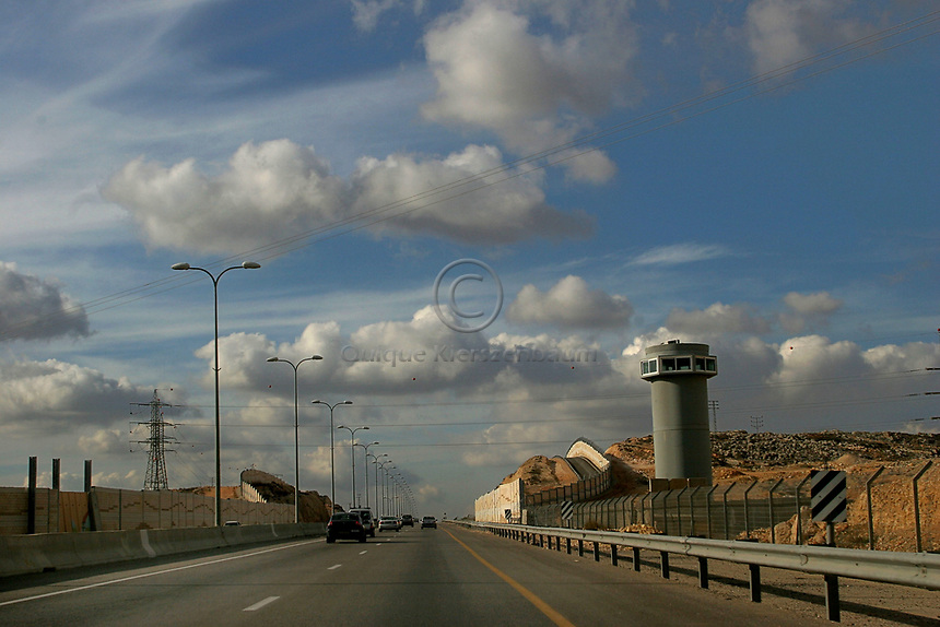 A portion of Road 443 in the West Bank surrounded by walls, by fences and watching towers blocking the Palestinian villages from the road, December 2007.