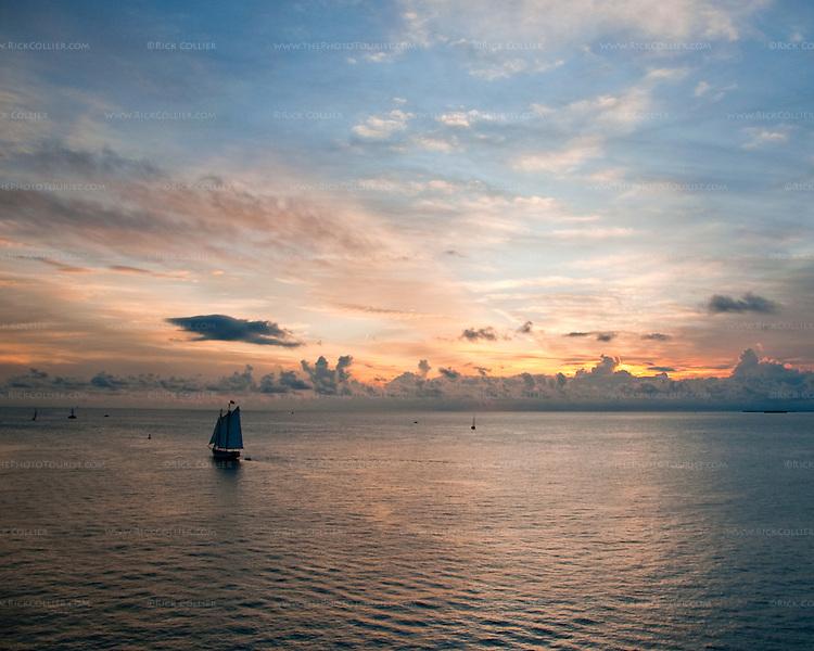 Tourist sailing cruises return to port at sundown.  Key West, Florida, USA.