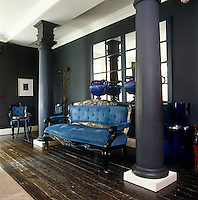 In a lounge of the G Hotel in Galway an antique sofa upholstered in deep blue velvet sounds a sumptuous note against the anthracite grey walls and dark floorboards