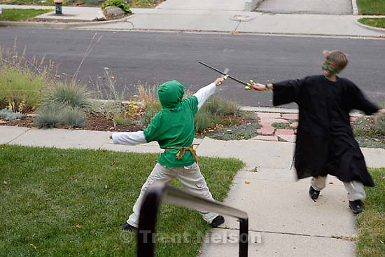 Nathaniel Nelson and Noah Nelson swordfighting out front on Halloween<br />