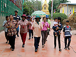 Worshipers dance the ramwong as musicians accompany them parading around the buddha statue