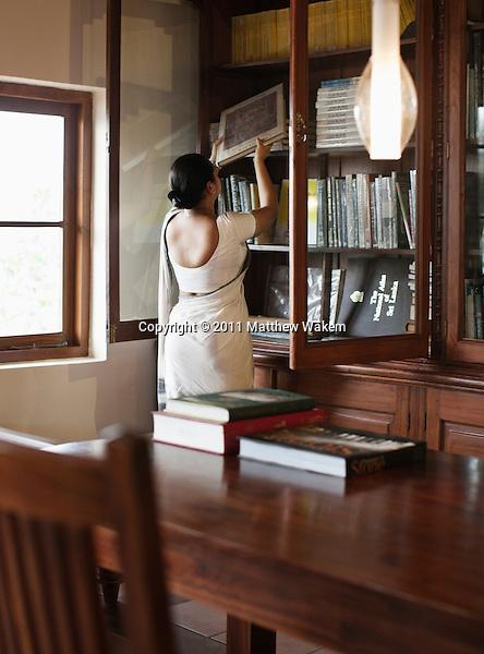 A woman arranges books on a bookshelf at the library at Saman Villas, Aturuwella, Bentota, Sri Lanka.