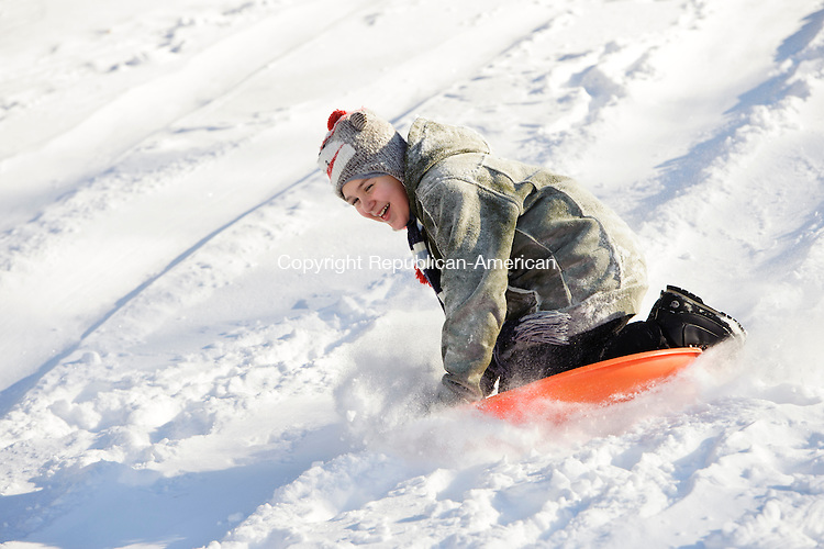 WATERBURY, CT - 3 January 2014-010314EC05--   Roberto Fontanez, 11, of Waterbury, flies down a snowy hill on a sled while playing in Fulton Park Friday afternoon.  Erin Covey Republican-American.