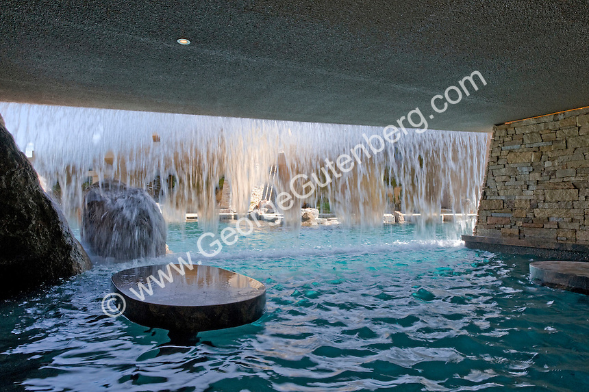 Daytime view of cave behind swimming pool waterfall for entertainment. Swim-up bar