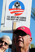 "Phoenix, Arizona. January 19, 2013 - ""I'll keep my guns, you keep the change,"" reads this sign seen during Saturday's pro-guns rally in Phoenix. As President Barack Obama proposed new gun regulations last week, gun owners demonstrated against it with national ""Guns Across America"" rallies to defend the Second Amendment. Dozens showed up at the Arizona State Capitol, many of them carrying weapons. Photo by Eduardo Barraza © 2013"