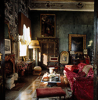 The walls of this sitting room are clad in black marble and the red velvet furnishings add a splash of colour and a sense of drama to this gothic room