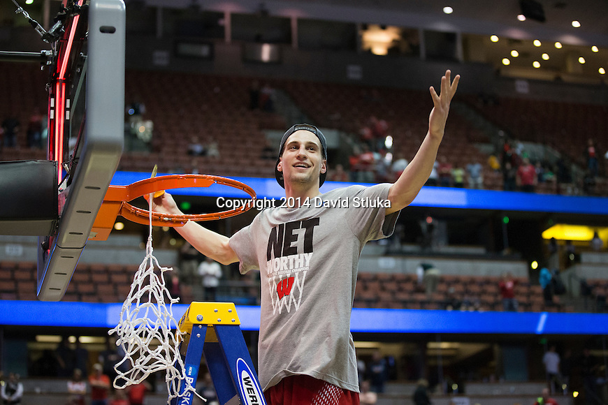 Wisconsin Badgers Ben Brust cuts down a piece of the net after the Western Regional Final NCAA college basketball tournament game against the Arizona Wildcats Saturday, March 29, 2014 in Anaheim, California. The Badgers won 64-63 (OT). (Photo by David Stluka)