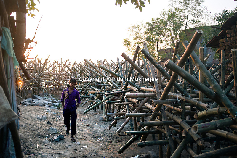 A boy walks along an array of bamboo cross- meshes which are to be placed along the banks on an emergency basis to stop erosion. According to the current Member of Legislative Assembly, say that these bamboo structures are very weak and of no use at all and the authorities should come out with a more permanent solution. Kholshi village, Murshidabad District, West Bengal, India.