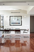 A spacious, contemporary dining area. The dining chairs are a 1950s Marcel Breuer design in a burgundy-brown leather and the dining table is crafted from wenge and seems to float in mid air.