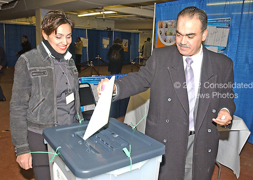 Doctor Mahdi S. Abdullah, M.D., of Mount Vernon, New York puts his completed ballot in the ballot box as he votes in the Iraqi election in New Carollton, Maryland on January 28, 2005.  Doctor Abdullah, a Baghdad-born internist, fled Iraq in 1993 after several of his relatives were killed by Saddam Hussein's regime.  He expressed joy at voting in the first free Iraqi election during his lifetime...Credit: Ron Sachs , CNP..(RESTRICTION: NO New York or New Jersey Newspapers or newspapers within a 75 mile radius of New York City)