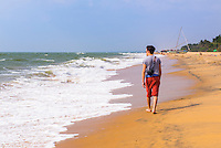 Tourist on holiday walking along Negombo Beach on the West Coast of Sri Lanka, Asia. This is a photo of a tourist on holiday walking along Negombo Beach on the West Coast of Sri Lanka, Asia.
