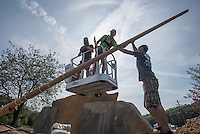 NWA Democrat-Gazette/J.T. WAMPLER Matt Long (from left) and Mike Koontz, both of Bentonville, and Joshua Ayers of Fayetteville hoist a new flagpole into place Tuesday Sept. 22, 2015 in Bella Vista. The crew from Sign Studio placed the flagpole amid a cluster of nearly 30,000 pounds of rock that will bear a new sign welcoming people to Bella Vista. The letters will be backlit with LED lights that have the ability to change colors.