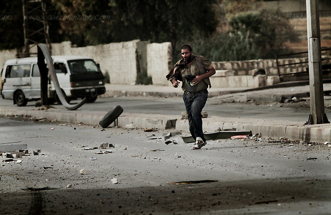 Members of the Al-Baraa Bin Malek Katiba, a part of the Free Syria Army under the Al-Fatah brigade, attempt to rescue a man who was shot by a sniper positioned in a building across the street on a main road that crosses the Bustan Al-Bashar district of Aleppo on October 20, 2012. Several vehicles drove past this man as he looked up in desperation (no one stopped because of the risk of being shot by the sniper). At a moment's notice, the man stood up and began to run towards the members of the Free Syria Army. As he approached the other side of the street, he was shot a second time, falling to the ground. Free Syria Army soldiers crawled through the ground to reach him and pulled them towards a vehicle that rushed him to the hospital. It is not known if he survived. Three civilians were shot on this main road in the space of three hours by the same sniper. ..© Javier Manzano............