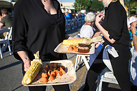 NWA Democrat-Gazette/CHARLIE KAIJO Athena Gay of Tie 1 On catering serves a Kansas City strip loin with corn on the cob, glazed-roasted carrots and MJ BBQ sauce, Saturday, June 9, 2018 on Emma Ave. in Springdale. <br /><br />Back for its 3rd year, this popular event brought hundreds of guests together for a lively, friendly community dinner of multiple courses served under the night sky&acirc;&euro;&rdquo;right down the middle of Emma Avenue. Past attendees raved about the special experience of dining al fresco with family and friends, as well as meeting new neighbors.