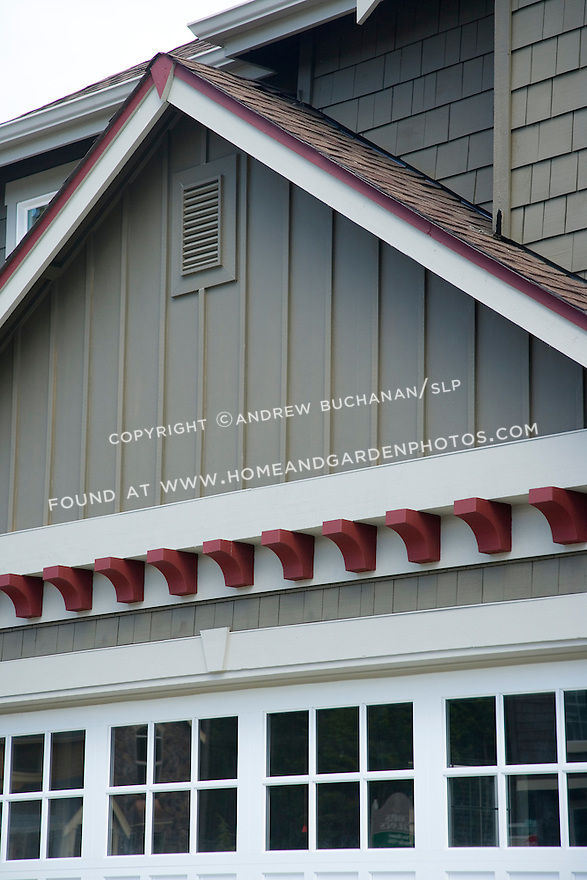 Detail of the shingled and board and batten facade, garage door window lights, and dark red trim of a two story, 2-story builder spec home in a suburban development near Olympia, WA.