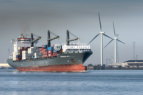 The container ship, Pomerenia Sky leaves the Porty of Tilbury and steams downriver on the River Thames.