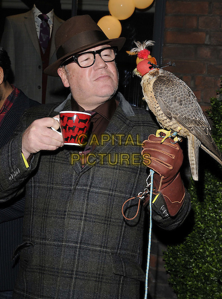 Ray Winstone.The Gresham Blake store launch party, Gresham Blake, Commercial St., London, England..January 25th, 2012.half length black grey gray check plaid tartan tweed coat jacket hat glasses hat brown bird animal feather glove mug drink beverage funny .CAP/CAN.©Can Nguyen/Capital Pictures.