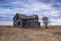An abandoned farmhouse sits quietly on the plains of Colorado.