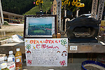 "An illustrated letter written by Miho Suzuki, 43, to her daughter Kana, who was swept away with 73 fellow elementary school students and teachers during the March 11 tsunami, restson  an ad hoc  shrine outside Okawa elementary school in Ishinomaki, Miyagi Prefecture, Japan on 07 Sept. 2011. ""Kana, if you read this letter, please come home. Mummy and Daddy are waiting for you,"" a part of the letter reads. Photograph: Robert Gilhooly"